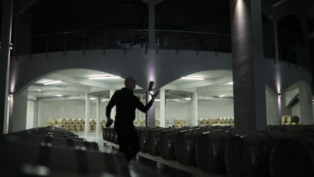 Man practicing flairtending in dark wine cellar alone