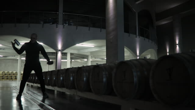Man practicing flairtending in dark wine cellar