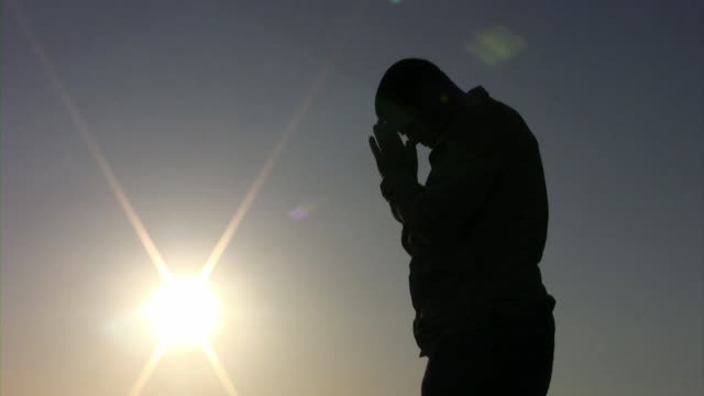 Man Praying (HD) A silhouetted man prays towards the sun.(1080i source) 笹 stock videos & royalty-free footage