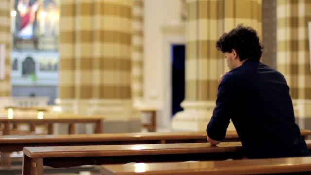 man prays in a church video
