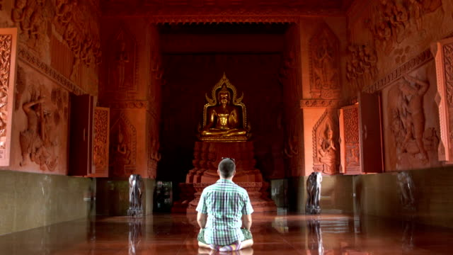 a man prays kneeling in front of a buddha statue in a buddhist temple - buddha video stock e b–roll
