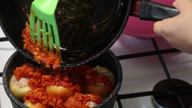 vídeos de stock e filmes b-roll de a man prepares bell peppers stuffed with minced meat and rice. adds sauteed carrots with ketchup to it. - paprica