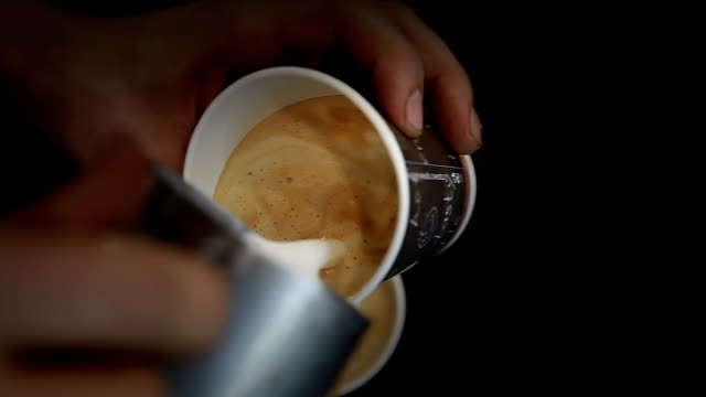 a man prepares cappuccino flavored. pouring the hot milk into the coffee. - junk food stock videos and b-roll footage