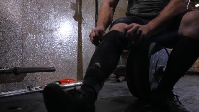 vídeos de stock e filmes b-roll de man preparing before weightlifting - dureza