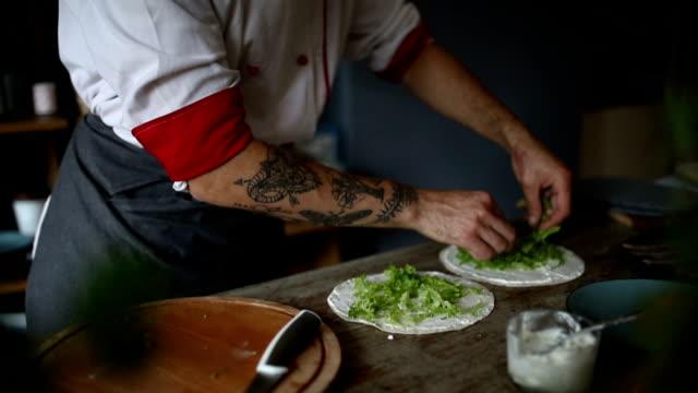 mann bereitet burrito - tätowierung stock-videos und b-roll-filmmaterial