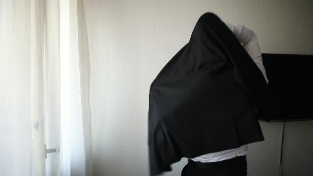結婚式の日の準備をしている男、黒のスーツを着て - 着る点の映像素材/bロール