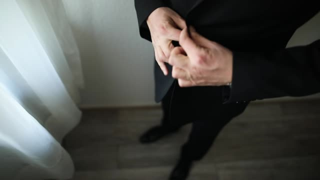 Man preparing for a wedding day, trying on black suit