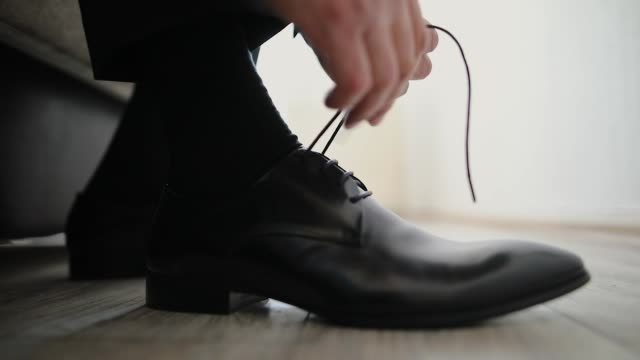 Man preparing for a wedding day, tying shoe laces close-up Man preparing for a wedding day, tying shoe laces close-up human foot stock videos & royalty-free footage