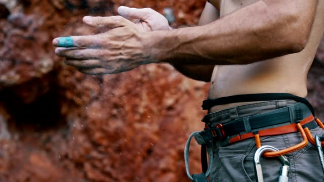 Man preparing for rock climbing Close up video of male rock climber taking a chalk from bag and putting it on his hands before climbing on the rock. b roll stock videos & royalty-free footage