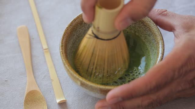 mann bereitet grüne tee-matcha in einer schüssel auf blauer oberfläche. drink ist eine reiche quelle von antioxidantien und polyphenolen. - grüner tee stock-videos und b-roll-filmmaterial