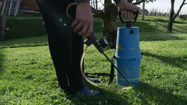 vidéos et rushes de homme prépare des pesticides pour la pulvérisation d'un arbre - herbicide