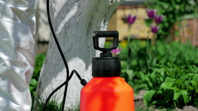 Man preparing pump sprayer for work in the garden video