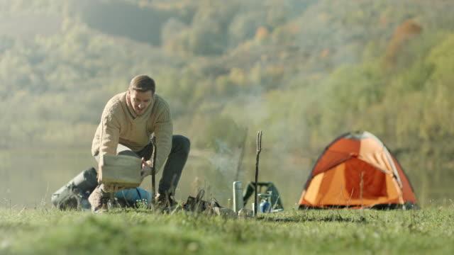 Man preparing wood for campfire video