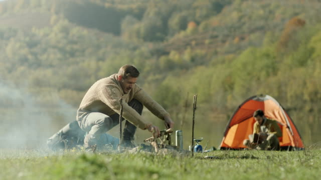 Man preparing wood for campfire while his friend book reading by the tent video