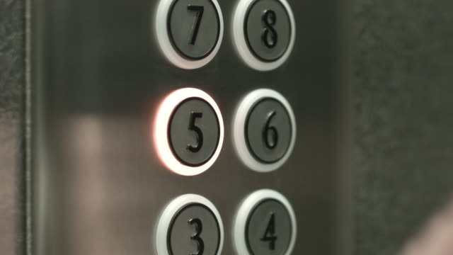 Man presses a button the fifth floor in an elevator video