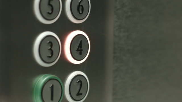 Man presses a button the fourth floor in an elevator video