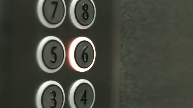 Man presses a button the sixth floor in an elevator