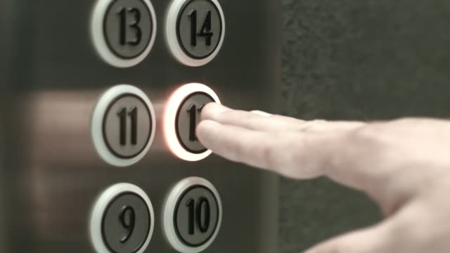 Man presses a button the twelfth floor in an elevator video