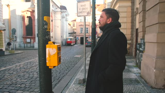 Man presses button at pedestrian crossing. Tram traffic in Prague has priority.