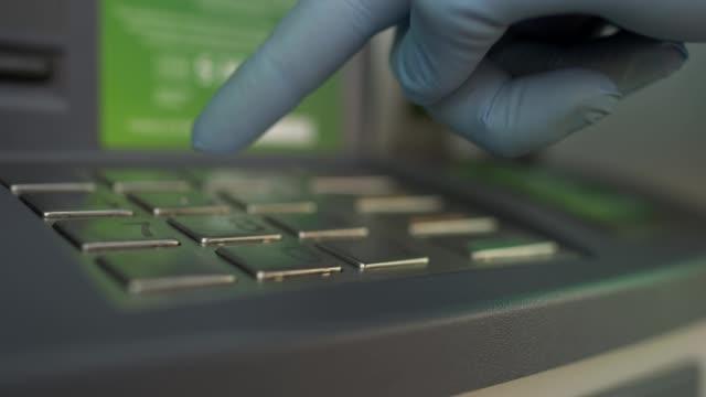 en man trycker på knapparna vid en bankomat för att ta ut pengar i medicinska skyddshandskar. begreppet skydd och säkerhet under koronaviruspandemin, covid-19, karantän - skyddshandske bildbanksvideor och videomaterial från bakom kulisserna