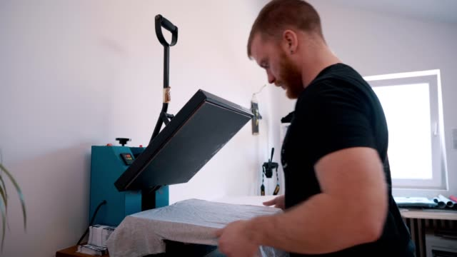 Man printing text on t-shirt Bearded, young man is printing text on t-shirt with heat press  machine in workshop. printmaking technique stock videos & royalty-free footage