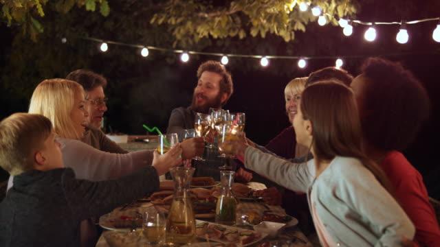 Homem de DS, propondo um brinde para os membros de sua família em um jantar de churrasco - vídeo