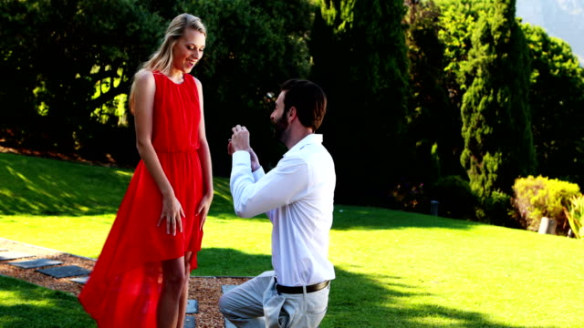 Man proposing a woman with a ring on his knee 4k video