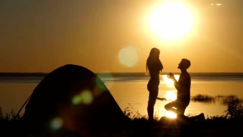 uomo che propone donna amata sulla spiaggia al tramonto - fidanzato video stock e b–roll