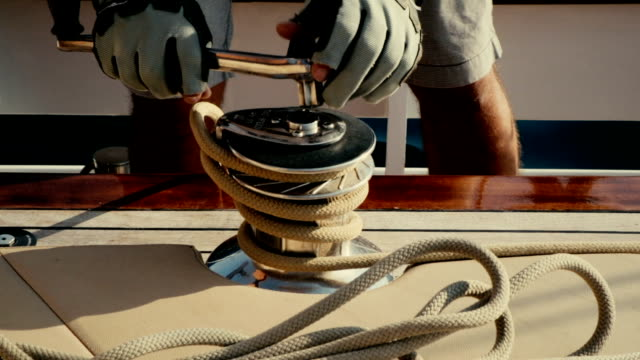 Man pulling ropes, winding sheets around winches. Sailing video