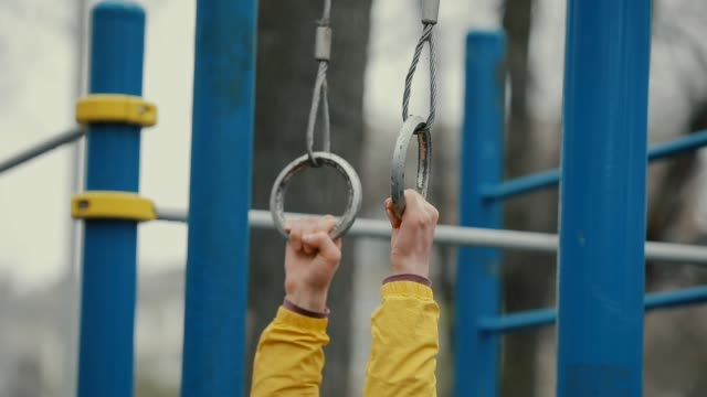 Man pull-ups on rings in park video