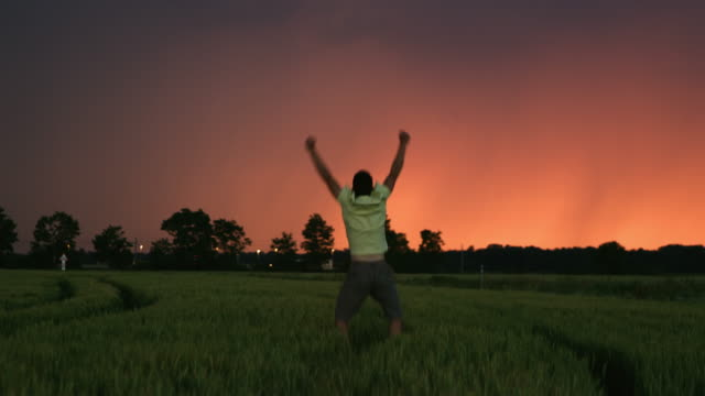 DS Man punching the air in a field of wheat at dusk Dolly shot of a man jumping and raising his arms to the sky in the middle of a field of wheat with colorful sky at dusk. anticipation stock videos & royalty-free footage