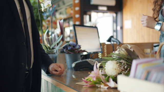 Man purchasing flowers paying with cash in florist's store giving money Man purchasing flowers paying with cash dollars in florist's store giving money to cashier taking bouquet from saleswoman. Commerce, business and people concept. paper currency stock videos & royalty-free footage