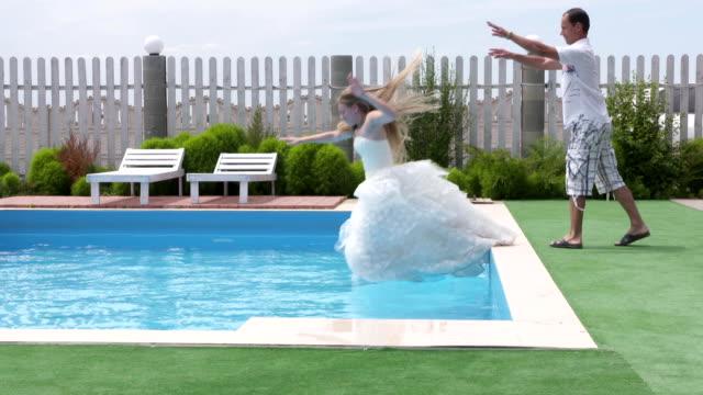 vidéos et rushes de l'homme pousse jeune mariée bar dans l'eau comme une blague drôle - lieu sportif