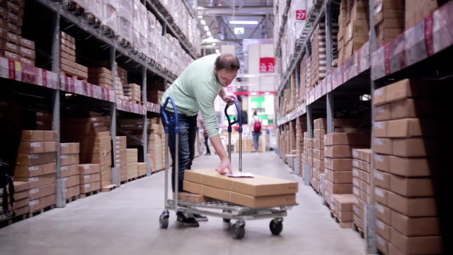Un homme poussant un chariot dans un entrepôt. Il est vérifier sa liste et boîtes nécessaires de prendre - Vidéo
