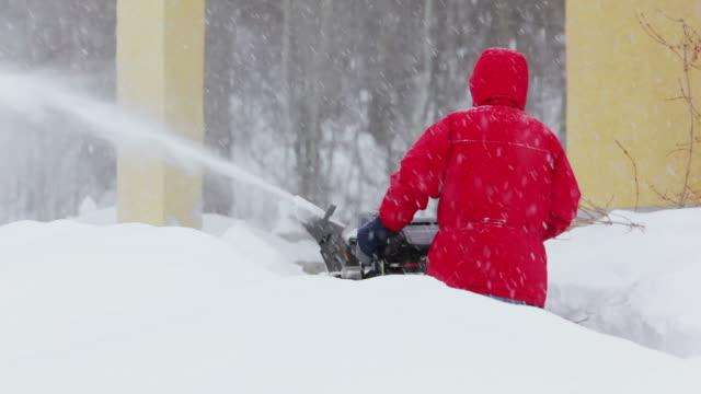 vidéos et rushes de homme pousser souffleur de neige - blizzard