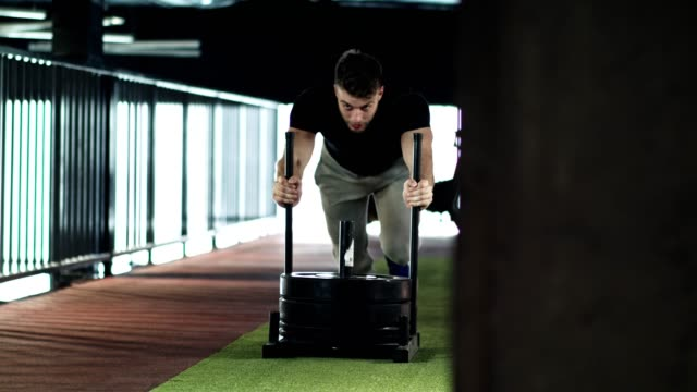 Man pushing weight sled in the gym