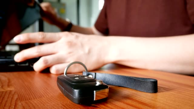 man put car key down on wooden table and using laptop computer on background - indoor scene - key ring stock videos & royalty-free footage