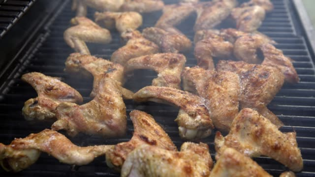 4K, Man put salt to pieces marinated chicken on BBQ grill. Grilling barbecue