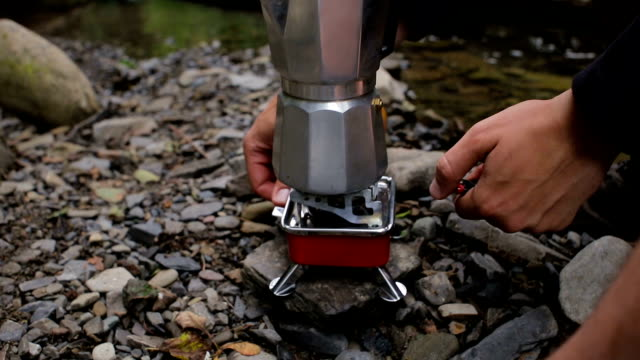 A man puts a coffee maker on a stove in a camping on the river bank video