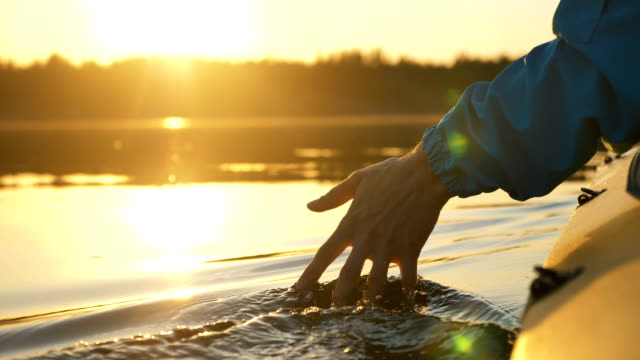 man puts fingers down lake kayaking against backdrop of golden sunset, unity harmony nature - vídeo
