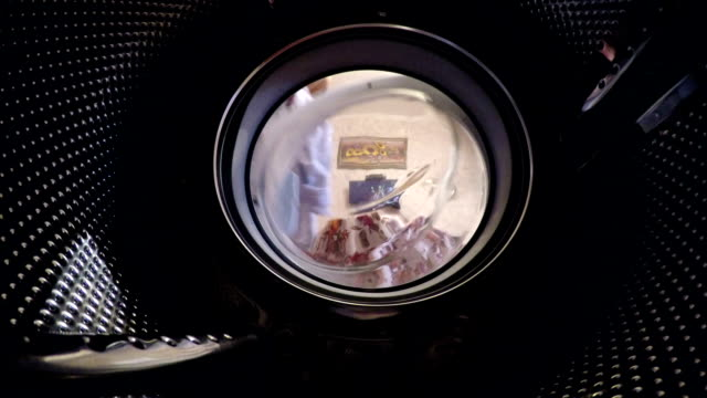 Man puts his shirts into the washing machine. video