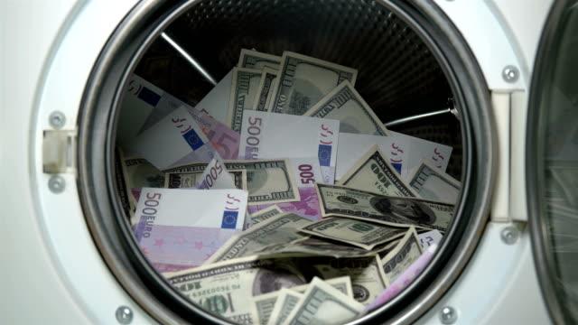 man lägger pengar i tvättmaskinen - dirty money bildbanksvideor och videomaterial från bakom kulisserna