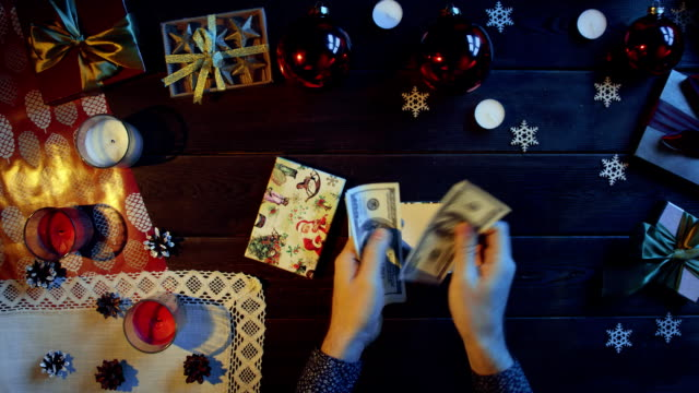 男は、木製の装飾が施されたテーブル、トップ ショット ダウンに新年のギフト ボックスにお金を置く ビデオ