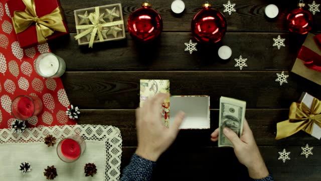 男は、木製の装飾が施されたテーブル、トップ ショット ダウンのクリスマス ギフト ボックスにお金を置く ビデオ