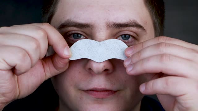 A man puts on and removes a strip for the nose from black dots. Coal cleaning strips from blackheads and comedones. The concept of personal care.