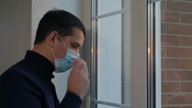 Man puts on medical surgical mask before going out video