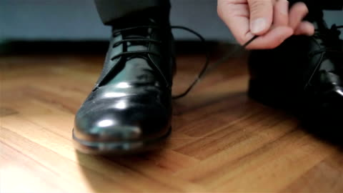 vidéos et rushes de l'homme se met sur les chaussures - chaussures