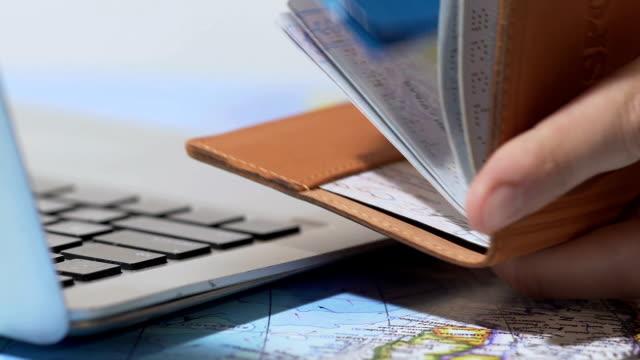 uomo che mette i biglietti aerei in passaporto, facile prenotazione e servizio di consegna a domicilio - fare una prenotazione video stock e b–roll
