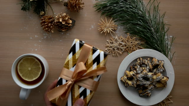 Man putting christmas present on a wooden table with christmas decoration. Top view. Close up. Cozy Christmas mood video