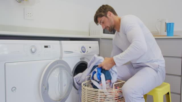 自宅の洗濯機に服を置く男 4k - 洗う点の映像素材/bロール